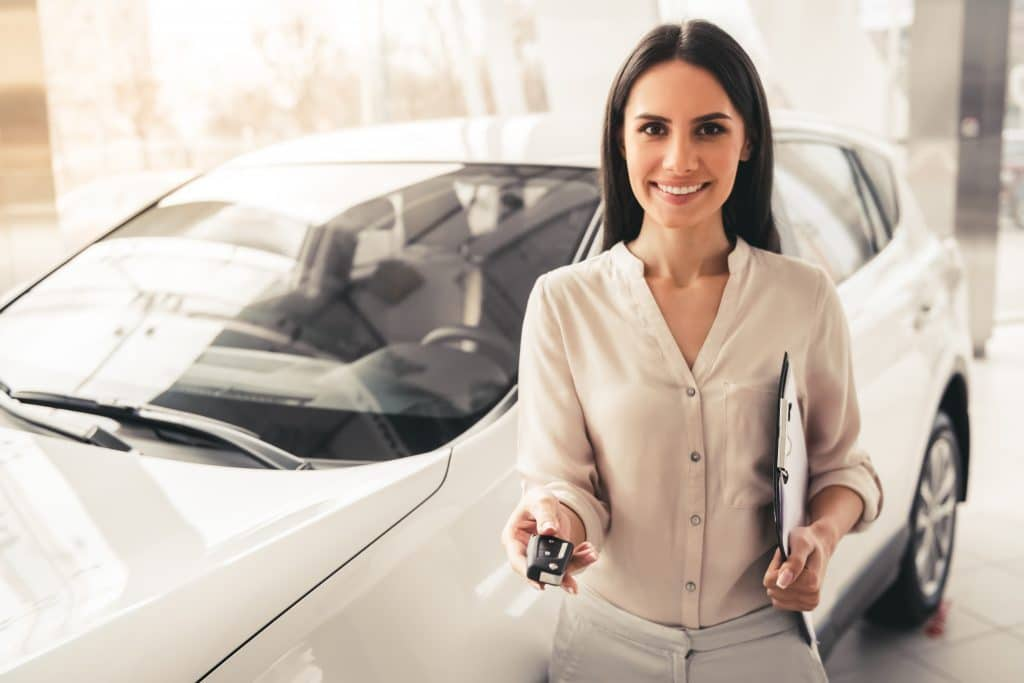 Winnipeg auto finance woman in dealership handing you the keys