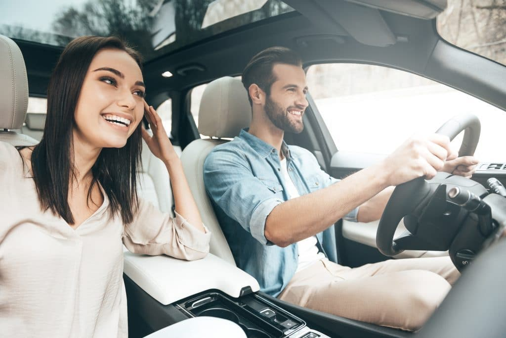 happy man and woman in car after being approved for an auto loan