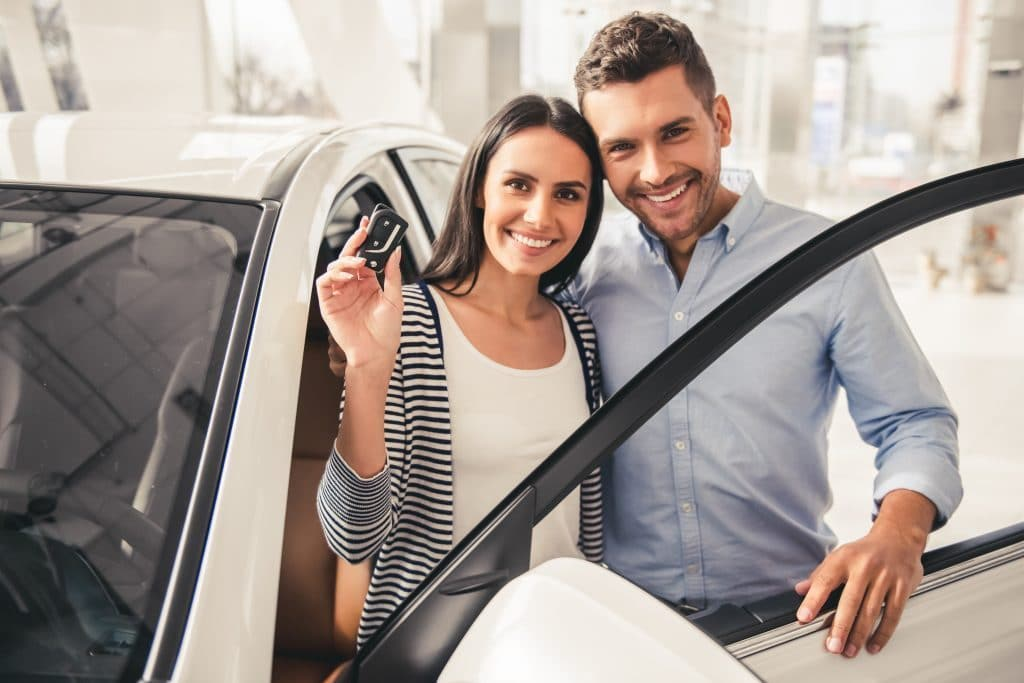 Woman holding car keys and man standing by their new car in a dealership