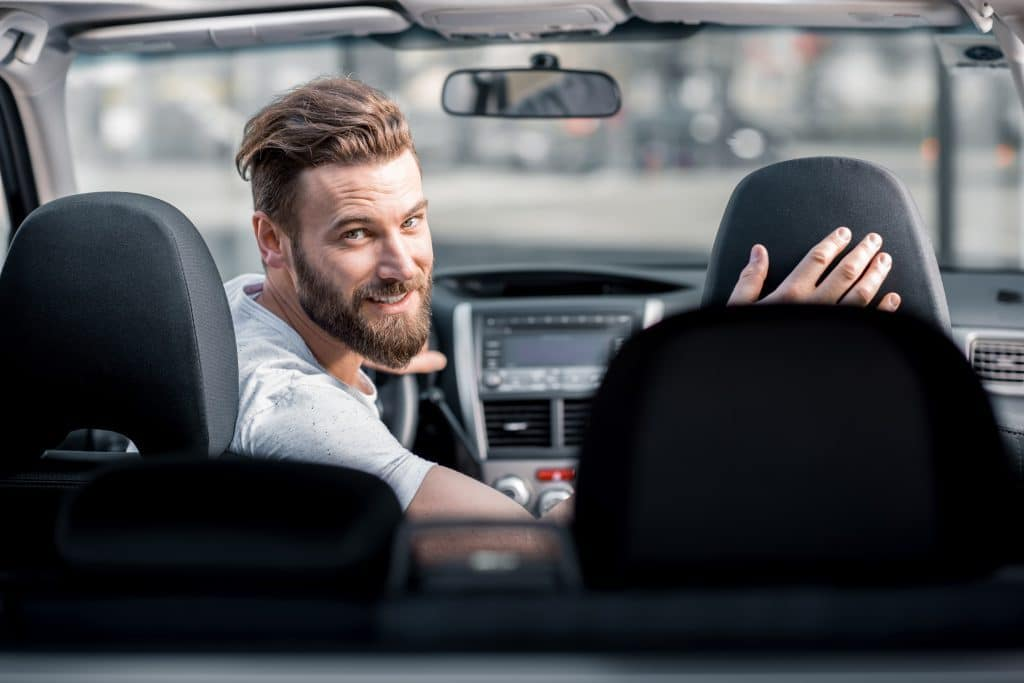 young man with beard in car looking back