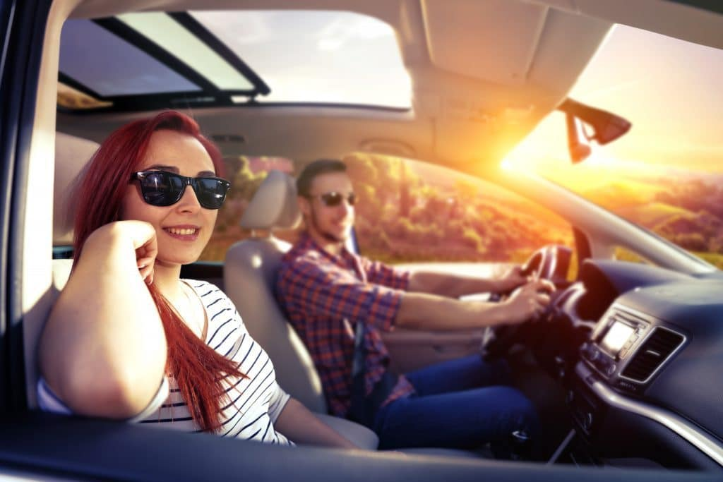 girl and man in car with sun shining